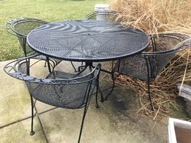Selection of outdoor furniture and decor including a black Woodard wrought iron table with 4 chairs.