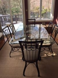 72 x 42 in Glass Table with beautiful iron-work support. Includes 6 iron, upholstered chairs.