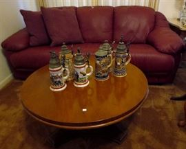 Burgundy sofa, German beer steins, coffee table