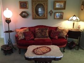 Beautiful settee adorned with pillows.  Lamps, tables, footstools, and pictures also in this grouping.