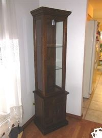 """Wood curio cabinet, lighted, with glass door, sides and shelves, brass hardware and enclosed bottom storage area.  68"""" tall, 18"""" wide, 14"""" deep."""
