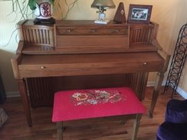 Aerosonic piano by Baldwin.  The bench has a beautiful embroidered cover.  Lots of sheet music for sale also.