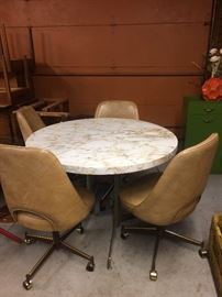 This lovely marble like table and 4 of the 6 rolling dining chairs... table comes with a matching leaf (not pictured)