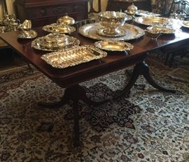 Unique pieces of the grape pattern of silver plate displayed on the Duncan Phyfe style dining room table.  The room size rug is included in the sale