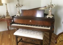 Schiller baby grand piano with upholstered bench. Piano was manufactured in 1936.