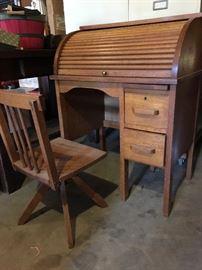 Miniature roll top desk in golden oak with swivel chair.