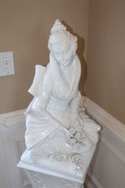 Porcelain statue on pedestal-woman picking flowers