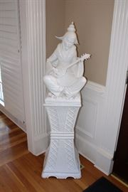 Porcelain statue on pedestal-man playing instrument