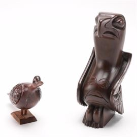 Totems by Ilata Eagle and Small Carved Bird Sculpture: A pairing of bird sculptures. This includes a carved figurine of a warm red tone wood, with extending small head with protruding beak, black eyes, and textured wigs. It stands on a bevelled base, with no discernible maker's mark. It is paired with a stonewre totemic eagle scupture by Totems by Ilata of Anchorage Alaska.The bird is dark brown with an arching beak, deep set eyes, and wings tucked into its sides before the extending front, ornamented with abstract features. It has an original maker's label underneath.
