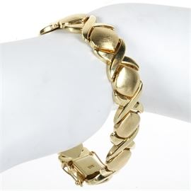"Italian 14K Yellow Gold ""X"" and ""O"" Bracelet: An Italian 14K yellow gold bracelet featuring alternating ""X"" and ""O"" shaped links with a box tab closure."