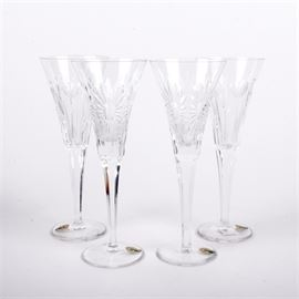 "Two Pairs of Waterford Champagne Glasses: Two pairs of Waterford Crystal champagne flutes. Includes one pair of toasting flutes in the ""Love"" pattern and one pair of flutes in the ""Health"" pattern. Each flute features a Waterford sticker and an etched Waterford maker's mark on the base."