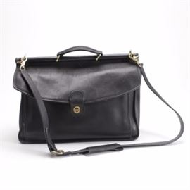 Leather Coach Briefcase: A leather Coach briefcase. The piece is black in color with gold tone hardware and closures. It has an adjustable strap with a zipper compartment along the sides and is labeled Coach with a serial number 1170-218.