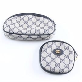 """Gucci Cosmetic Bags: A pair of Gucci cosmetic bags. This selection includes a Gucci cosmetics bag in the designer's signature monogram canvas with leather detailing and a zipper closure. The bag is marked with a serial number, 039-922-3045. Also included, a round Gucci cosmetics bag in the designer's signature monogram canvas with leather detailing and a zipper closure. The bag is marked with a serial number, """"039-904-0215""""."""