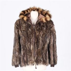 Raccoon Fur Jacket: A raccoon fur jacket. The jacket features a fully lined hood and interior with a zipper closure, drawstring hem, and knit cuffs. The mottled fur pelts are vertically pieced and stitched.