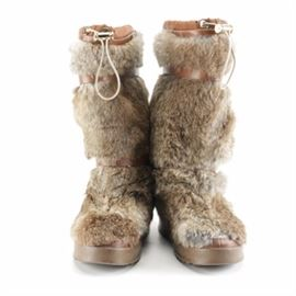 Tory Burch Fur Boots: A pair of Tory Burch fur boots. These boots showcase rabbit fur to the exterior with brown, leather-like straps with gold tone hardware. The lining is comprised of brown shearling and features an adjustable cord to the tops of the boots. They are labeled by Tory Burch.