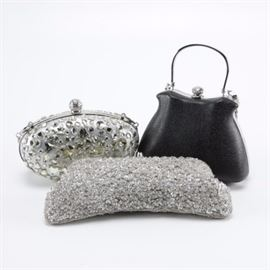 Clutch Handbags Including V2 by Vanessa: An assortment of clutch handbags. This assortment features three bags, including a silver tone bag ornamented with an array of faceted beads that has a hinged opening and chain shoulder strap, a textured black bag with silver tone handle and chain shoulder strap, and a silver sequin bag with a kissing closure and optional shoulder strap by V2 by Vanessa.