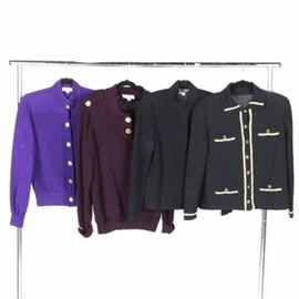 Collection of Women's St. John Sweaters: A collection of St.John sweaters. Featured one cable knit purple sweater with gold tone buttons and a mock collar, a black button up sweater with cream accents and button accents on the chest and bottom, a black sweater jacket with hidden buttons and a mock collar, a burgundy sweater with gold tone button neckline and buttons accents at the shoulders and cuffs.