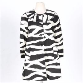 Kate Spade Zebra Coat: A Kate Spade zebra coat in a size small. The coat is a trench coat style that showcases a white and black striped design that has accents of black rounded enamel buttons in a gold tone setting. Other features include a rounded collar with a bow, long sleeves and slanted side pockets with flaps and a white lining.