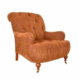 Tufted Lounge Chair: A tufted lounge chair. This chair features button tufting and rusty brown colored paisley upholstery. The top of the back is scrolled, with slightly rolled arms and a thick seat front. There is brass-toned nailhead trim along the bottom edge, and the chair rests on square back legs and turned bun front feet with casters. This piece matches item 17BOS053-149.