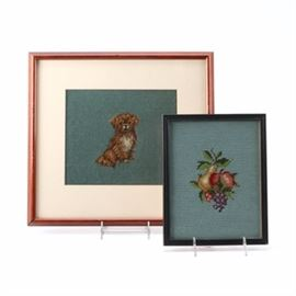 Pair of Framed Needlework Art: A pair of framed needlepoint art. This collection includes needlepoints depicting a bouquet of fruit and another of a cocker spaniel. Each is mounted under glass in black or brown wood frames with hanging wire present to verso. No signature or artist name is present to either piece.