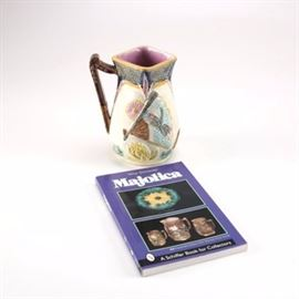 Victorian Majolica Pitcher and Reference Book: An antique Victorian Majolica Jug together with a Shiffer Collectors book. The jug displays elements including the Japonesque aesthetic movement themes first displayed in Wedgwood's Argenta Bird and Fan pattern. This piece was made in the period between 1890-1900 by an unidentified English firm. The book is titled Majolica by Mike Schneider and was published by Shiffer.