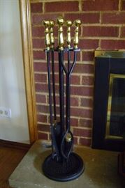 Heavy wrought iron fireplace tool set with brass handles.