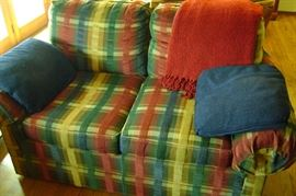 """Comfortable plaid love seat is 64"""" long including various pillows."""