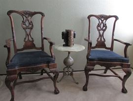 Chippendale Host and Hostess Arm Chairs - Ball and Claw Feet, Hand Carved  Backs, Arms and Legs.  One of two Luna Bella marble topped tables. African bookends on table