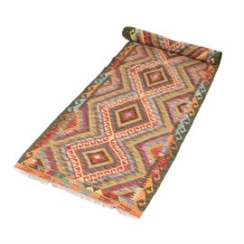 Handwoven Turkish Kilim Runner: A handwoven Turkish Kilim runner. This all wool rug is woven in a geometric diamond pattern in a vibrant red, yellow, brown, orange, blue and olive green palette. The natural gray wool warp fringe is knotted. The rug is unmarked.