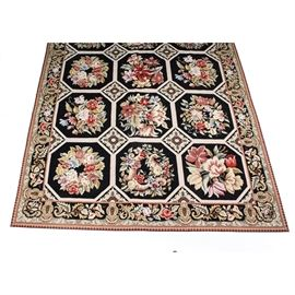 "Handcrafted French Style Needlepoint Rug: A handcrafted French style needlepoint rug. This elaborate rug features an alternating floral and medallion design in a color scheme of mauve, forest green, mulberry, pink, olive green, coral, and forest green atop a black ground. The rug has a sizable compound border in a correlating design within the same palette. The rug is marked ""73735""."