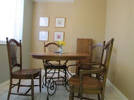 """Ethan Allen Round kitchen table with one extra leaf, arm chair, three no-arm chair. Wrought iron table base and oak wood (chairs and table) diam 46"""" start price$400.00"""
