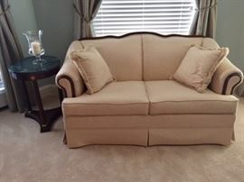 Broyhill love seat cream with mahogany details around the frame.