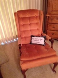 """Orange arm chair; pillow: """"Age is a number, and mine is unlisted."""""""