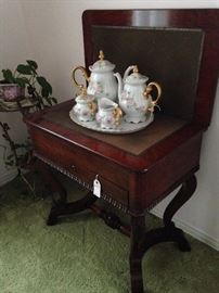 The antique game table can be used in a different way. This tea set was hand painted by Mrs. Roscoe Etter while living in China.