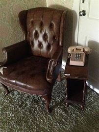 Brown leather wingback chair and small side table