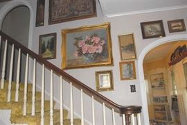 The staircase to this 1940s home is lined with original art and vintage prints.