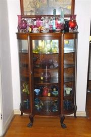 Mirror-backed, paw-footed, oak curved glass curio circa 1890. Full of art glass, Fenton and more!