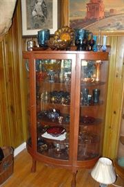 Large Oak curved glass curio is overflowing with Carnival Glass, including pitchers, egg tray, vases and bowls. Another nearby curio cabinet is full of pink depression glass.