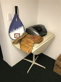 TENNIS RACQUETS BASEBALL GLOVES ATOP TABLE WITH FOLDING SIDES