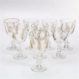 Lenox Wine Glasses: A selection of eight Lenox crystal glasses. Each has a gold tone trim around the lip with faceted ovals around the exterior that have intricate renaissance style designs inside them and the cup stands on a lobed and faceted stem that terminates in a circular base. They come in the original box.