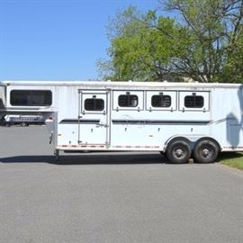 2002 Sundowner Horse Trailer: A 2002 Sundowner four horse trailer. The two axle trailer features a gooseneck hitch and aluminum body with a gross vehicle weight rating of 12,200 lbs. The trailer was designed to haul four horses. The trailer features a slant load with padded dividers. Sliding and drop-down windows are available for each horse as well as top vents. An escape door is accessible for the first horse for quick access. The interior also features lighting. A four saddle rack is at the rear of the trailer. A rubber bumper at the rear and two exterior lights at the back allows for safe loading and unloading. The trailer also features a tack/dressing room to the front. The room features a carpeted interior, sliding windows and top air vent. A door in the interior of the room opens to allow for easy access to the horses. The trailer has a VIN of 13SVE282721VB5345.