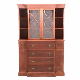 Mahogany Breakfront Cabinet: A mahogany breakfront cabinet. This piece features crenelated molding above six compartments and a glass-fronted cabinet, with two interior shelves. This top section rests on four drawers, with the top drawer having a hinged drop-down front. On either side, there is a storage cabinet with optional interior shelves. Unmarked.