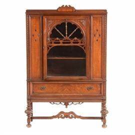 Vintage 1920s Oak China Cabinet: A vintage 1920s English-style oak china cabinet. This cabinet has a carved top molding, diamond incised motifs to the sides and a glass panel door with carved wood overlay. The inside of the cabinet has two shelves. Below, is a drawer with brass-tone figural pulls and a carved bottom molding. It rests on turned, bun feet with a scroll carved stretcher.