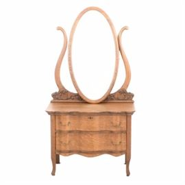 Early 20th Century Quarter Sawn Oak Chest with Oval Mirror: A circa early twentieth century, quarter-sawn oak chest with an oval mirror. This two-drawer chest features a scalloped top, serpentine front with brass pulls, and curved legs. The attached oval mirror has a beveled edge and is held between two scrolled arms with carved acanthus mounts to the base.