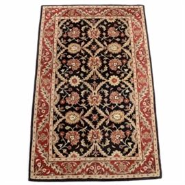 Persian-Inspired Wool Area Rug: A Persian-inspired wool area rug. This rug has a main field with palmettes and circular vines in beige and red against a black background. Beyond that, there is an outer border with vines and palmettes against a red field and a black outer edge. There are no maker's labels.