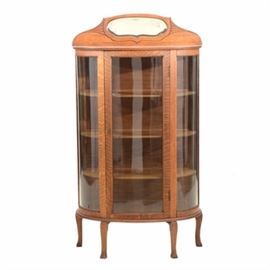 Vintage Oak Display Cabinet: A vintage china or curio display cabinet, in oak. It has a gallery edge to the top with a small mirror, a curved front with glass panes to the door and sides, and three removable wood shelves to the interior. Unmarked.