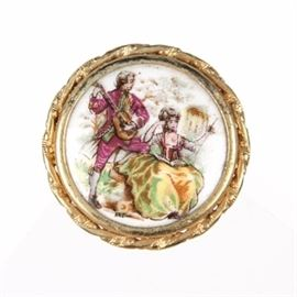 """P. Pastaud Limoges Porcelain Brooch: A P. Pastaud Limoges brooch. The round gold tone twisted frame encases a painted image of a man serenading a woman with his guitar as she sits with a wand and book of music. The back of the brooch is stamped """"p. pastaud Limoges France""""."""