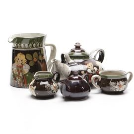 """Bavarian Pottery Tea Set: A painted four piece Bavarian tea set. The pottery teawares are decorated with blonde children. The collection is accompanied by an additional teapot with marks on the bottom indicating it was premium from the Ming tea company. The group includes a pitcher, large teapot, cream jug and sugar bowl as well as the additional pot. Inscribed marks on the underside read """"Bavaria""""."""
