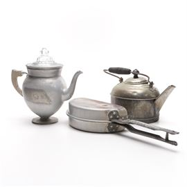 Aluminum Coffee Pot, Kettle, and Omelette Maker: A collection of aluminum kitchenware. This selection features a stemmed wood handled coffee pot, with a clear domed top, and removable percolator. Also included is a semi circular handled omelette maker and a tea pot.
