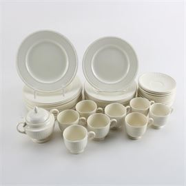"""Wedgwood """"Edme"""" China Set: A Wedgwood Edme china set. This lot of forty-three pieces includes eleven dinner plates, eleven salad plates, twelve saucers, eight footed teacups, and one sugar bowl. The off-white china features embossed ribbing to the sides and lips of the dishes. The plates are marked to the base """"Wedgwood – Edme – Made In England"""" with the model number marked in the surface. The sugar bowl lid is marked underneath """"Wedgwood – Embossed Queens Ware – Made In England – U.S.A. Patent August 1.1922""""."""